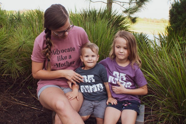 Mother and two kids wearing statement shirts. Mother's shirt reads Advocate like a Mother and the kids' shirts read Be Kind finger-spelled in ASL